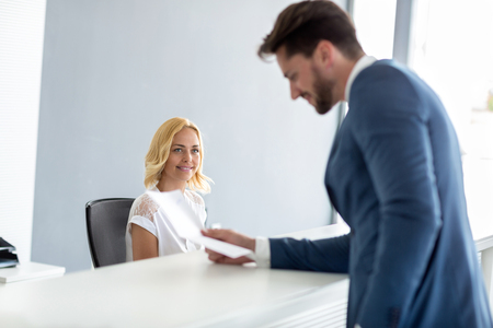 hotel receptionist: Young pretty female receptionist look at handsome businessman at check desk
