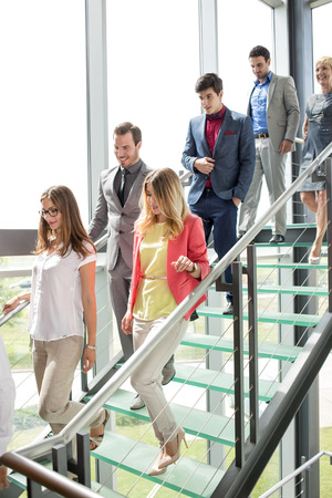 down stairs: smiling business people walking down stairs in building Foto de archivo