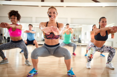 Smiling blond female trainer with headset doing squats with fitness group indoor Stock Photo