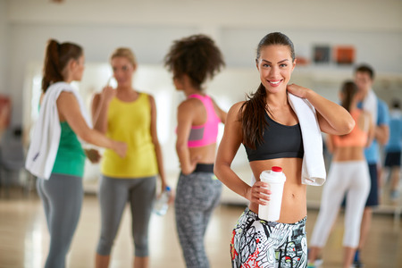Lachende vrouw met een fles drank eiwit en een handdoek na de training in de gymzaal