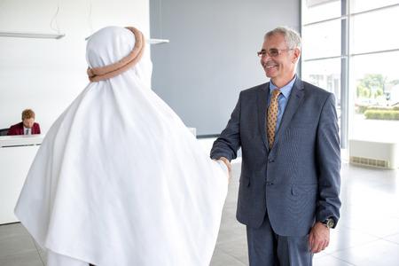 negocios internacionales: director maduro del apretón de manos con el socio de la empresa de Arabia