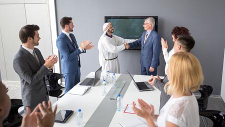 negocios internacionales: socio árabe con el director de la empresa hace negocio exitoso y apretón de manos