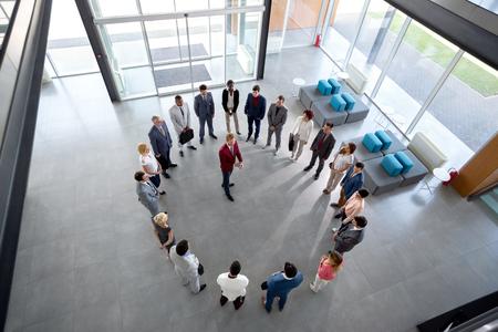 젊은 이사가 회사 홀의 서클에있는 직원들과 만남