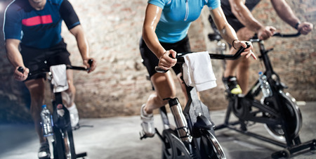 sports clothing people riding exercise bikes, cardio fitness class Stock Photo