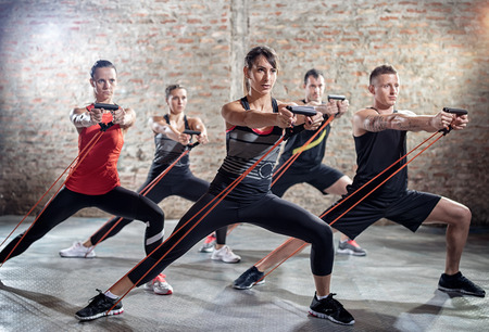 rubber band: young people doing workout with elastic band, modern workout class Stock Photo