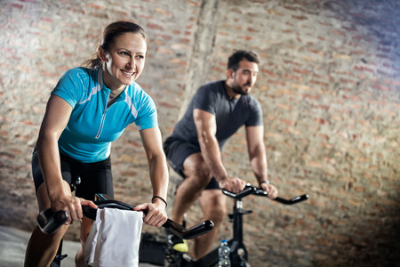 to spin: Smiling woman in sports clothing on cycling fitness training Stock Photo
