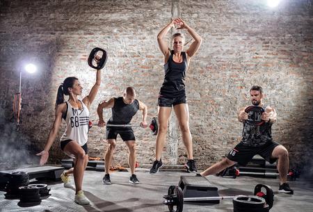 ropa deportiva: Grupo de personas en ropa deportiva haciendo ejercicio diferente Foto de archivo