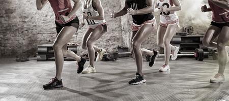 Grupo de mujeres alegres y positivos en la clase de entrenamiento de correr pose