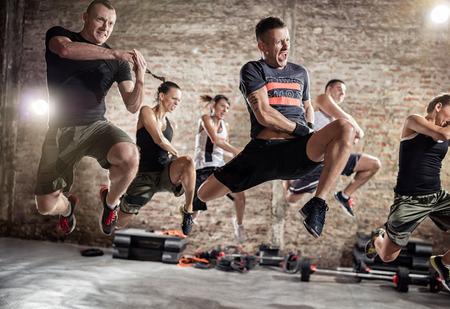 personas saltando: Grupo de personas que salta y la práctica de ejercicio físico cardiovascular