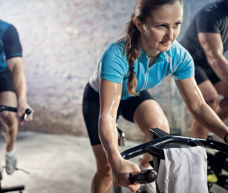 to spin: Woman on cardio exercising on bike, training, sport and healthy lifestyle Stock Photo
