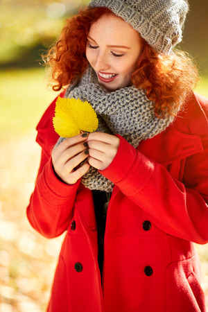 Smile redhead girl look yellow leaf in autumn Stock Photo