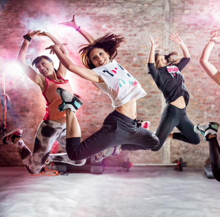 young group: Attractive girl in jump practicing dance workout Stock Photo