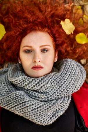 lying on leaves: Portrait of red haired woman lying on fallen leaves, top view