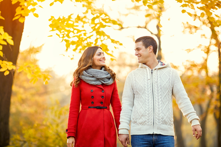 Romantic couple walking in park in autumn photo