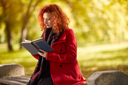 Red hair female read book in nature in October Stock Photo
