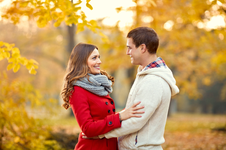 Smiling young woman and man in love in park at autumn photo