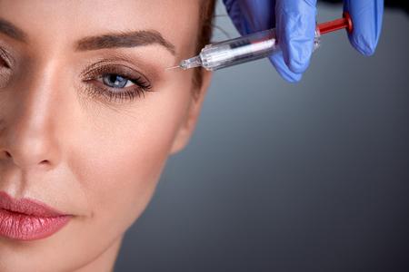 inyeccion: mujer de mediana edad en la terapia de rejuvenecimiento con botox Foto de archivo