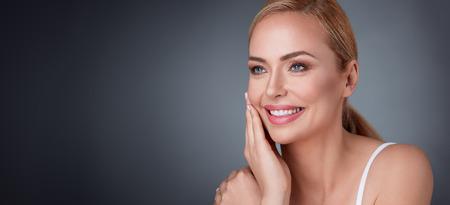 Lächelnde Frau mittleren Alters zufrieden mit ihrer Naturschönheit