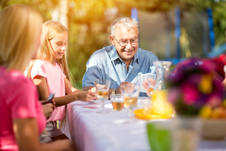 family playing: grandfather playing cards outdoors with family