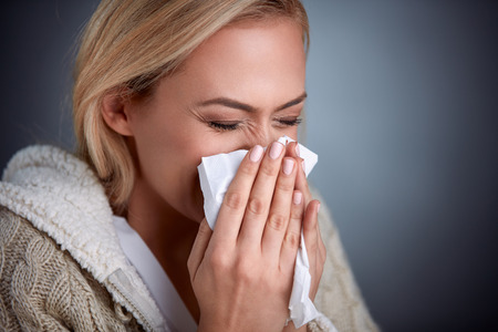 Cold woman holding handkerchieif blowing nose Stock Photo