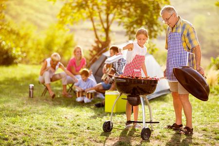 gelukkig gezin grillen van vlees op een barbecue