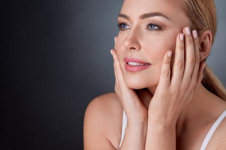 traitement: souriante femme aux épaules nues touchant le visage