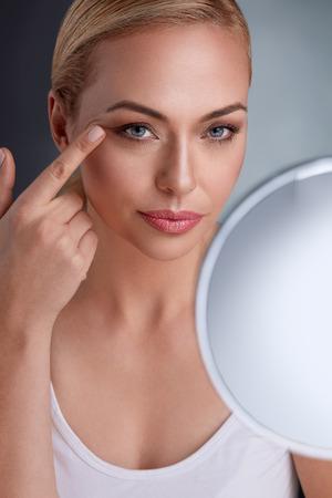 그녀의 완벽한 피부를 찾는 거울로 아름다운 여자