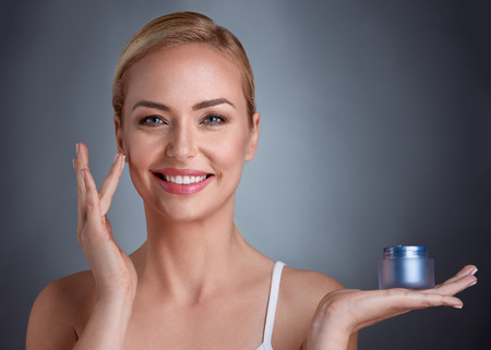 中年女性の完璧な美しさの自然派化粧品の手のひらにクリームを保持