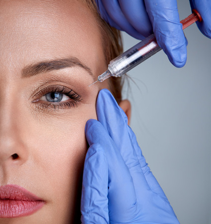 Portrait of a woman during surgery filling facial wrinkles, cosmetic is injected into skin around eyes