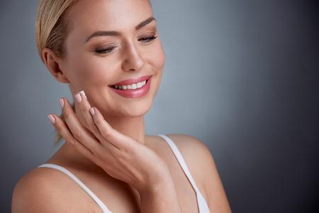 素敵な中年の女性顔のクリームを適用する笑みを浮かべて嬉しそう 写真素材