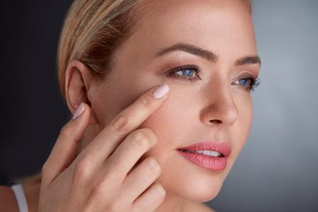 Middelbare leeftijd vrouw die huid op haar gezicht kijkt Stockfoto