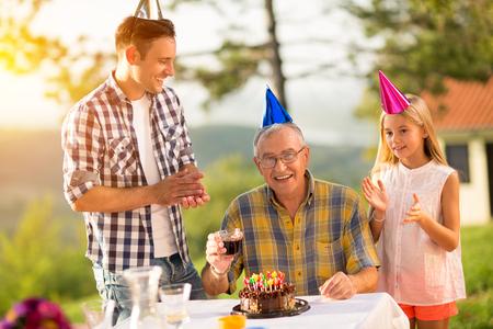 birthday presents: Happy senior man celebrating his birthday with family