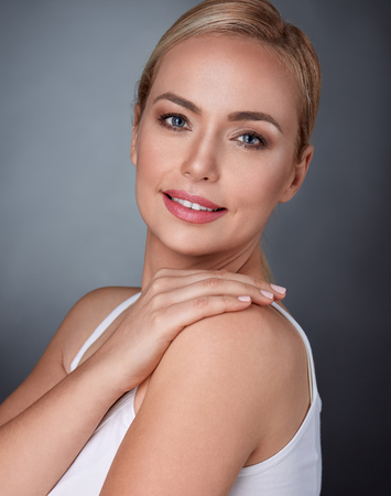 beautiful middle aged spa woman touching her shoulder