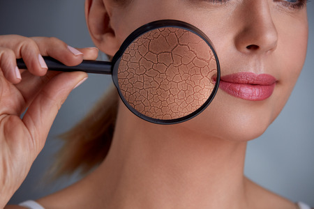 Woman holding magnifier and zoom damage on skin Stock Photo
