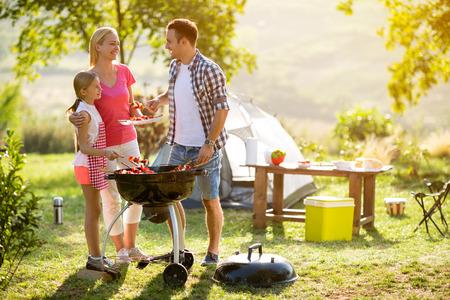 웃는 부모 캠핑에 딸과 고기를 굽고 스톡 콘텐츠