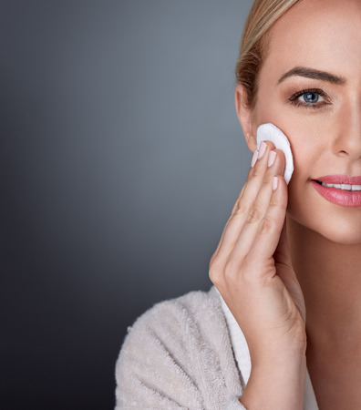 remover: Beauty and nourished in middle age, lovely woman cleaning her skin on the cheek