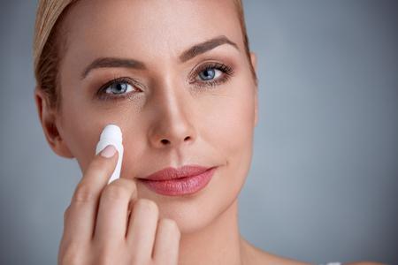 女性は、目の下のくまを削除します。 写真素材