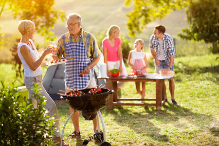 smiling grandparents drink wine by the barbecue for family Standard-Bild
