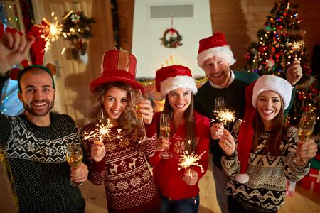 jóvenes felices que celebran Año Nuevo con Champaign y pulverizadores Foto de archivo