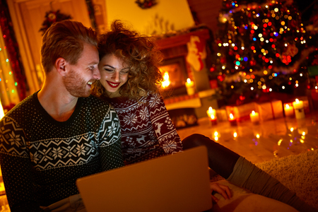 Young couple looking on laptop on Christmas eve Imagens