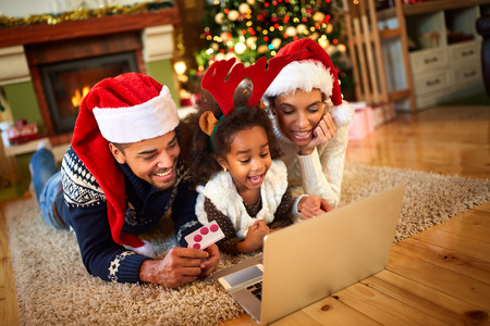 atmosfera: Smiling family lying on floor front of Christmas tree and looking at laptop