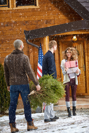 coming together: Men bringing New Years tree in mountain house Stock Photo