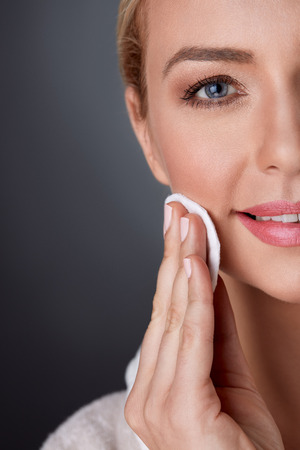 remover:  half portrait of middle-aged woman cleaning skin on face
