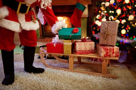 brings: Santa Claus brings presents in home next Christmas tree