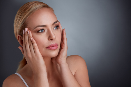 aging woman:  woman tightening skin on face to make you look younger, middle age and aging Stock Photo