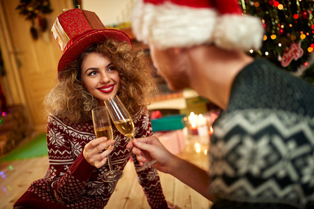 white winter: Pretty curly woman toasting with glass of white wine with boyfriend for Christmas