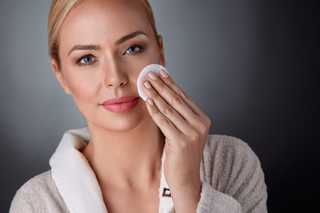 Middelbare leeftijd vrouw schoon haar huid, gezondheid en schoonheid Stockfoto