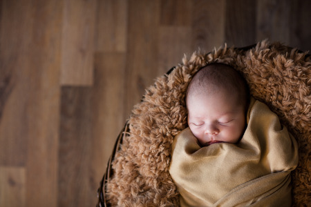 Cute newborn baby sleeps peacefully tucked in fluffy soft blanket    Stock Photo