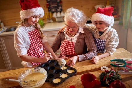 galletas de navidad: children enjoying with grandmother making Christmas cookies at home  Foto de archivo
