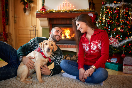 Happy female and male with dog together at Christmas eve